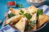 pic of samosa  - indian samosa filled with chicken curry on tray - JPG