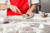 Midsection of female chef cutting ravioli pasta at messy commercial kitchen counter