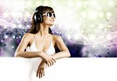 Young woman in white bikini wearing headphones. Place for text