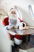 Portrait of man in Santa costume holding digital tablet in private jet