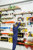 Rear view of mature worker reaching for bit case in hardware shop