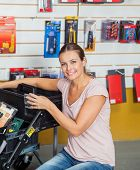 Portrait of smiling mid adult woman buying tools in hardware store