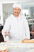 Portrait of smiling male chef dusting flour on ravioli pasta at commercial kitchen
