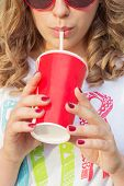 beautiful young girl in sunglasses in the summer warm day drinking coke through a straw with red