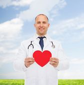medicine, profession, charity and healthcare concept - smiling male doctor with red heart and stethoscope over natural background