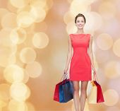 shopping, sale, christmas and holidays concept - smiling elegant woman in red dress with shopping bags over beige lights background