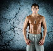 sport, bodybuilding, strength and people concept - young man with bare muscular torso standing over concrete wall background