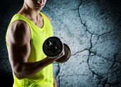 sport, bodybuilding, training and people concept - close up of young man with dumbbell flexing biceps over concrete wall background
