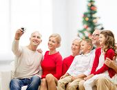 family, holidays, generation, home and people concept - smiling family with camera taking selfie and sitting on couch over living room with christmas tree background