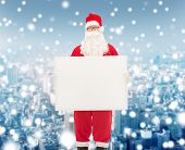 christmas, holidays, advertisement and people concept - man in costume of santa claus with white blank billboard over snowy city background