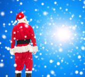 christmas, holidays and people concept - man in costume of santa claus from back over blue snowy background