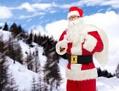 christmas, holidays, gesture and people concept - man in costume of santa claus with bag showing thumbs up over snowy mountains