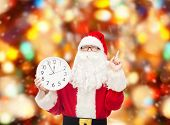 christmas, holidays and people concept - man in costume of santa claus with clock showing twelve pointing finger up over red lights background