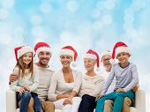 family, happiness, generation, holidays and people concept - happy family in santa helper hats sitting on couch over blue lights background