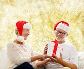 family, holidays, christmas, age and people concept - happy senior couple in santa helper hats with gift box over yellow background