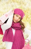 happiness, winter holidays, christmas and people concept - smiling young woman in hat and scarf with shopping bags over yellow lights background