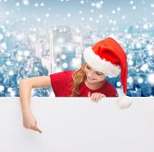 christmas, holidays and advertisement concept - happy girl in santa helper hat pointing finger on blank white board over snowy city background