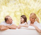 family, childhood, holidays and people - smiling mother, father and little girl over yellow lights background