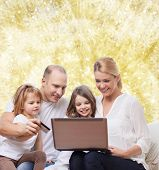 family, holidays, shopping, technology and people - happy family with laptop computer and credit card over yellow lights background