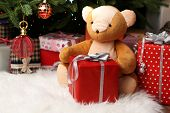 Teddy bear and gift boxes near Christmas tree, close-up