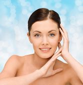 beauty, people and health concept - smiling young woman with bare shoulders over blue lights background