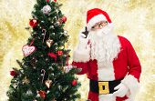 holidays, technology and people concept - man in costume of santa claus with smartphone and christmas tree over yellow lights background