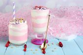 Cranberry milk dessert in glass and glass jar, on color wooden table, on light background