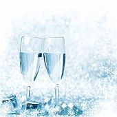 Glasses of champagne and silver gifts on glitter background