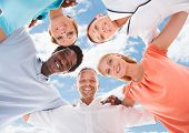 picture of huddle  - Directly below portrait of multiethnic business people forming huddle against sky - JPG