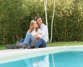 Romantic couple sitting by the pool in a sunny fall day