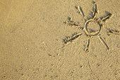 Sun drawn on the sand of a beach.