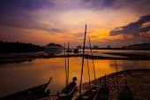 Silhouette of fisherman and traditional thai boats at Sam chong Tai, Phangnga Pprovince.