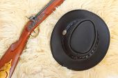 Cowboy hat and hunting guns on a sheep fur.