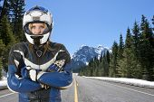 biker chick, wearing a motorcyclist suit and helmet, posing on a snowy road in beautiful mountain scenic, surrounded by large pine trees and the melting snow in the warm spring sun