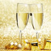 Glasses of champagne and ribbon on golden glitters