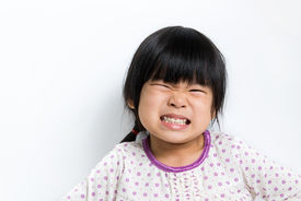 stock photo of pyjama  - Little Asian girl wearing pyjamas doing silly face - JPG