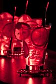 picture of collins  - Tom Collins cocktail shot on a bar counter in dim light - JPG