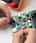 image of microchips  - Male hands close up checking voltage on a microchip - JPG