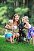 image of puppies mother dog  - girl and her little brother playing with dog on grass - JPG