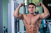 stock photo of physical exercise  - Muscular man working out with weights in gym - JPG