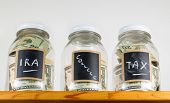 image of irs  - Three glass jars with chalk labels used for saving US dollar bills and notes for IRA tax and college funds - JPG