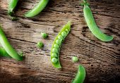picture of pea  - Some colorful green pea pods on old wooden background - JPG