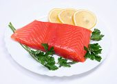 image of redfish  - Salmon steak with lemon slices and parsley on white plate - JPG