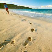 pic of footprints sand  - Woman at beautiful beach at Seychelles walking on sand - JPG