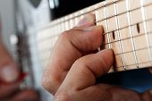 stock photo of fret  - Hands of man playing electric guitar with red pick closeup - JPG