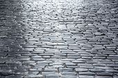 stock photo of cobblestone  - Grey cobblestone pavement with reflection after rain - JPG