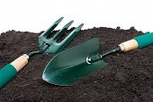 stock photo of household farm  - green gardening tools on black soil over white background - JPG