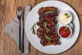 stock photo of ribs  - Grilled pork ribs in barbecue sauce on white plate top view - JPG