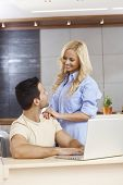 picture of fondling  - Young man sitting at table at home - JPG