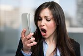 image of yell  - Portrait of an angry businesswoman yelling at phone - JPG